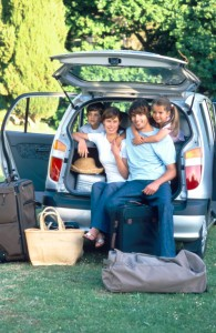 Family posing together in back of vehicle