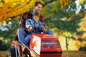 Father and son on tractor mower