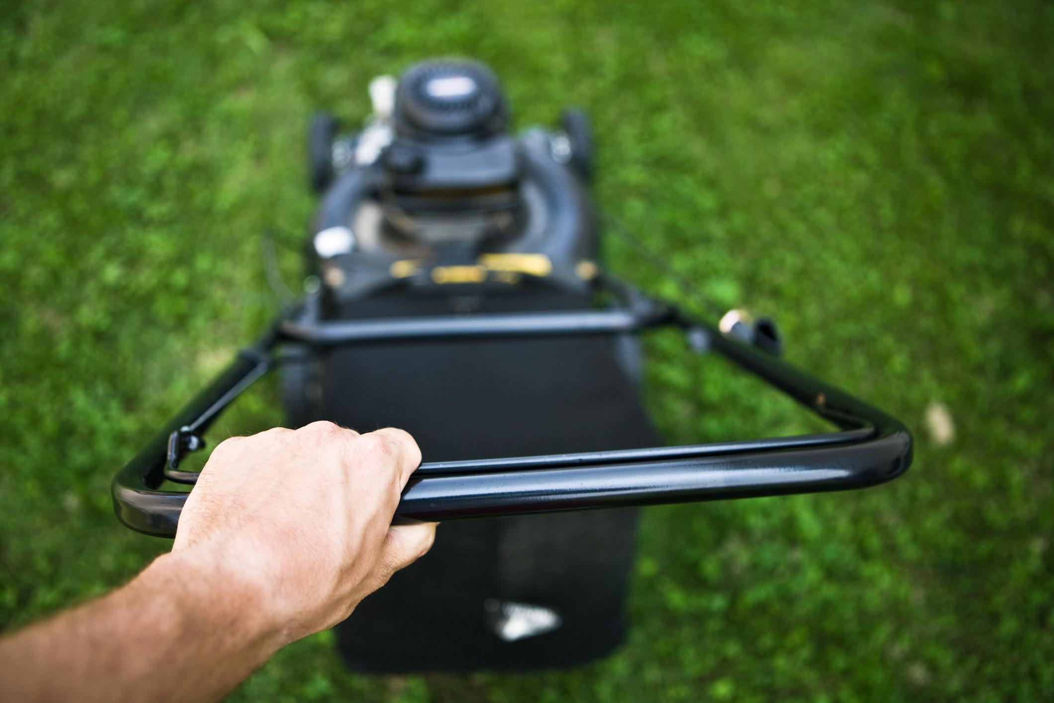 Hand of man pushing lawnmower
