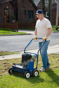 Man pushing power rake to de-thatch lawn.Please Also See: